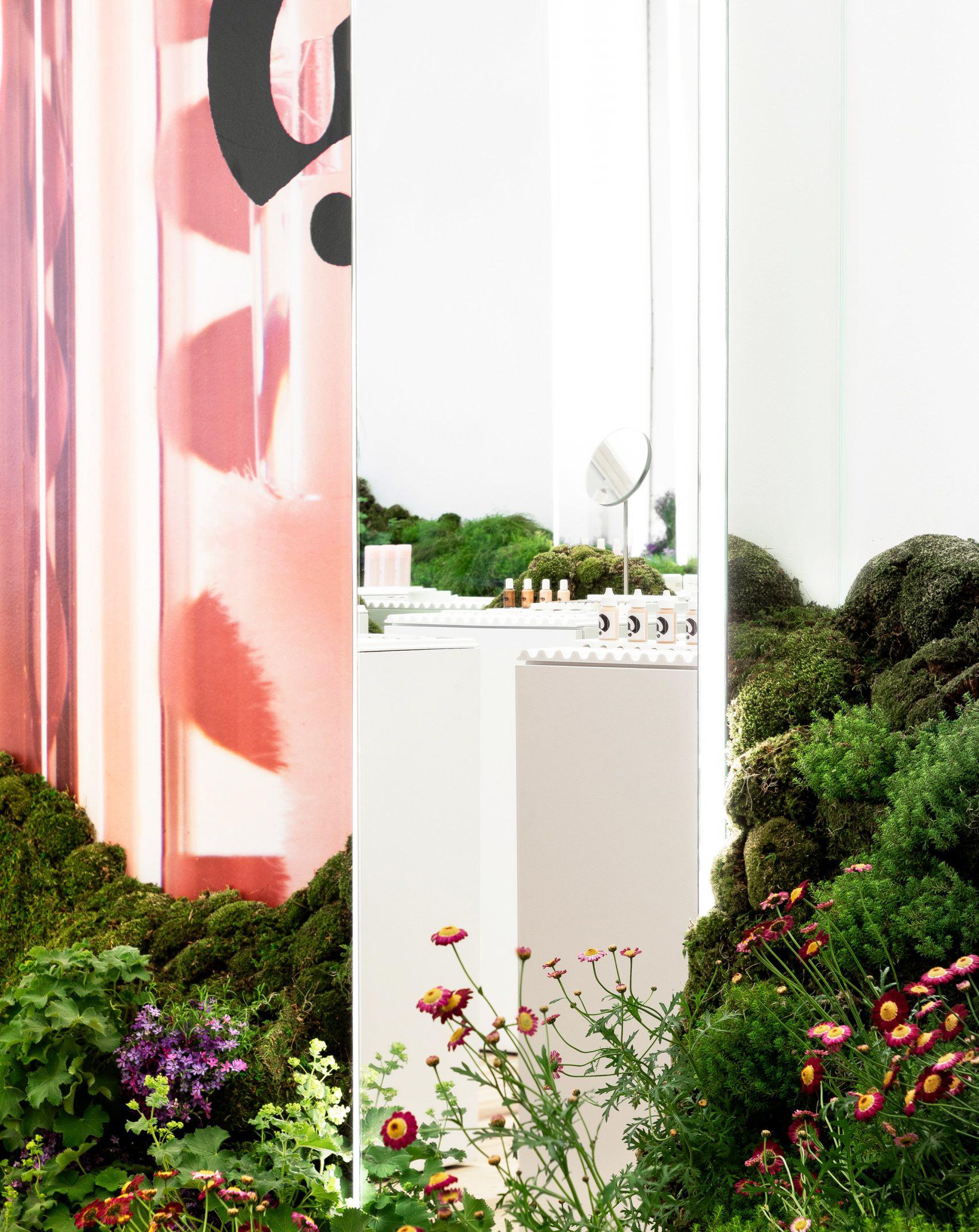 苔や花で覆われた丘が存在する対比が美しいコスメショップの店舗設計